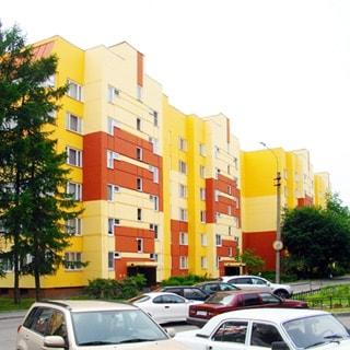 На фото: часть фасада панельного шестиэтажного многоквартирного жилого дома, фасад раскрашен в три цвета (оранжевый, ярко-желтый и песочный), без балконов, благоустроенная придомовая территория, газоны, деревья, тротуар, проезжая часть, припаркованные автомобили