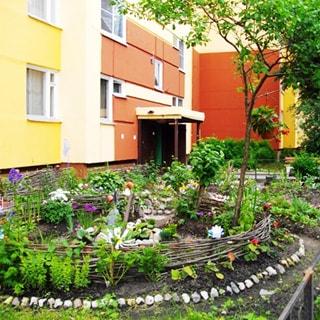 На фото: газон придомовой территории, художественно оформленная клумба, цветы, кусты, деревья, ландшафтный дизайн, газон огорожен низким металлическим ограждением
