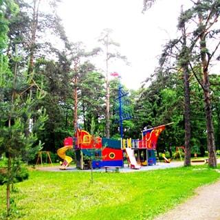 На фото: обустроенная детская площадка - городок, имитация парусного корабля, горки, домики, качели, песочница, газон, пешеходные дорожки, взрослые хвойные и лиственные деревья