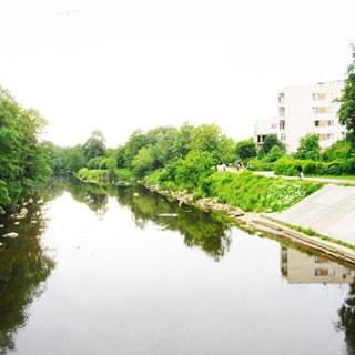 На фото: часть водной поверхности реки или канала, на левом берегу - деревья, отлогий правый берег частично покрыт газоном, частично облицован камнем, по верхнему краю - пешеходная дорожка, на дальнем плане - жилые многоэтажные дома и деревья