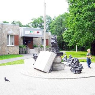 На фото: часть одноэтажного фасада здания или пристройки, стены облицованы камнем, над входом вывеска Детская библиотека, на переднем плане площадка со скульптурной композицией, изображающей книг и читающих гномов, территория вымощена тротуарным камнем, справа - парковая территория с газоном и деревьями