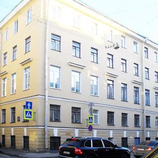 На фото: угол фасада кирпичного пятиэтажного многоквартирного жилого дома, фасад оштукатурен, без балконов, тротуар, проезжая часть, проезжающие автомобили