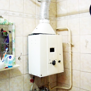 На фото: часть помещения ванной комнаты, прямо на стене - газовая колонка, под ней смеситель для ванной, слева на стене - зеркало, стены облицованы керамической плиткой