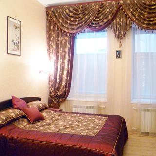 На фото: часть помещения жилой комнаты - спальни, два окна, под каждым окном - радиатор отопления, слева у стены - двуспальная кровать, на стене у кровати - бра, над кроватью - эстамп