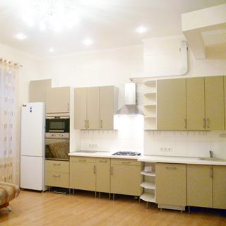 На фото: часть помещения кухни, слева - окно, справа от окна вдоль стены - кухонный гарнитур со встроенной кухонной техникой, газовая варочная панель, над ней - вытяжка, столы-тумбы и навесные шкафы, встроенная мойка, на потолке - люстра