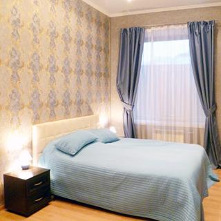 На фото: часть помещения жилой комнаты - спальни, одно окно, под окном - радиатор отопления, слева у стены - двуспальная кровать, слева и справ от кровати в изголовье - прикроватные тумбочки с настольными светильниками, стены оклеены обоями
