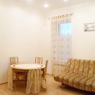 На фото: часть помещения столовой, одно окно, под окном радиатор отопления, слева от окна у стены - круглый обеденный стол, у стола - три стула, справа от окна - мягкий диван, стены - окрашены, на потолке - точечные светильники