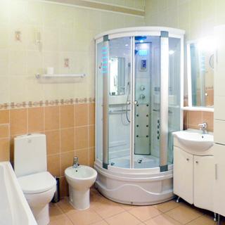 На фото: часть помещения совмещенного санузла, слева у стены - ванная, справа от нее - компактный унитаз, правее - биде, правее в углу - душевая кабина, справа от душевой кабины на тумбе - керамическая раковина со смесителем, над раковиной - зеркало с подсветкой, справа от раковины - высокий шкаф, полы и стены облицованы керамической плиткой