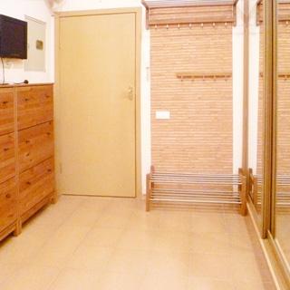 На фото: часть помещения прихожей, водная дверь, слева от двери у стены - шкаф для обуви, над ним монитор видеодомофона, справа от двери вешалка для верхней одежды, справа у стены - шкаф-купе с зеркальными дверцами, полы облицованы керамической плиткой