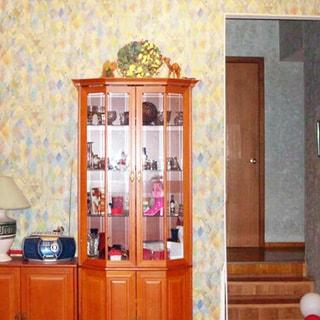 На фото: часть помещения жилой комнаты - гостиной, в центре у стены - сервант, слева от него - тумба с магнитолой и настольной лампой, справа - арка и ступеньки вверх в прихожую, стены оклеены обоями