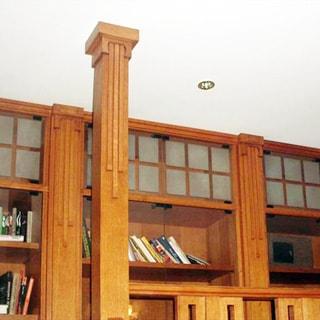 На фото: часть помещения жилой комнаты, прямо у стены от края до края - книжные шкафы, перед шкафом - деревянная колонна до потолка, на потолке - точечные светильники