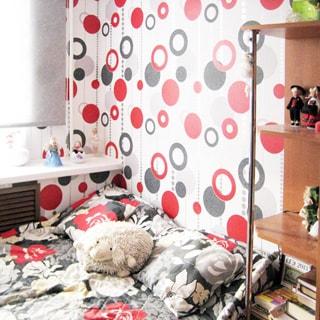 На фото: часть помещения жилой комнаты - детской, окно, у окна - разложенная кровать, рядом с кроватью - книжный стеллаж, стены оклеены обоями