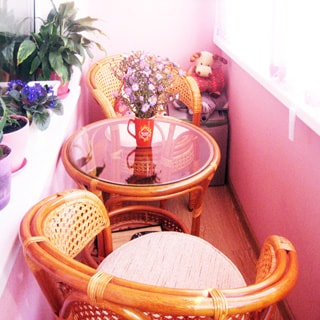На фото: часть помещения застекленной лоджии, два плетеных деревянных кресла и круглый журнальный столик со стеклянной столешницей, комнатные растения - на подоконнике