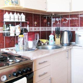 На фото: часть помещения кухни, от угла влево и вправо - встроенный кухонный гарнитур из тумб-столов с общей столешницей и навесных шкафов, в левой секции ближе к углу - металлическая мойка со смесителем, слева от тумбы с мойкой - 4-комфорочная газовая плита с духовым шкафом, на стене - полки с кухонной мелочью, фартук облицован керамической плиткой
