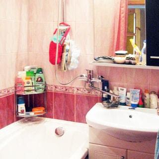 На фото: часть помещения ванной комнаты, прямо у стены - керамическая раковина на тумбе в виде шкафчика с дверцами, над раковиной на стене - полка, зеркало и шкафчик, слева - ванная, смеситель общий на ванну и раковину, стены облицованы керамической плиткой, на стене в углу - проволочные полки для ванных принадлежностей