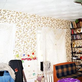 На фото: часть помещения жилой комнаты, два окна, под окном - радиатор батареи центрального отопления, у окна - диван, спрва у стены - книжный стеллаж, стены оклеены обоями