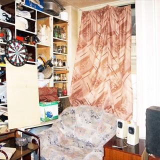 На фото: часть помещения жилой комнаты, окно, у окна - мягкое кресло, тумбочка и журнальный столик, слева у стены - стеллаж из полок, стены и потолок оклеены обоями