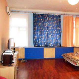 На фото: часть помещения жилой комнаты, три окна, слева у стены тумба с телевизором, над ней на стене - кондиционер, справа - часть разложенного дивана или кровати, полы - ламинат, на потолке - люстра