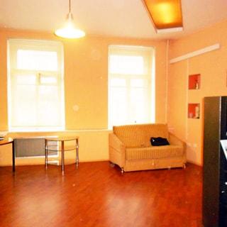 На фото: часть помещения жилой комнаты, два окна, у левого окна - два журнальных столика, у правого окна - небольшой мягкий диван, полы - ламинат, на потолке - люстра и светосекция