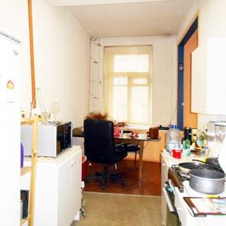 На фото: часть помещения кухни, окно, у окна - обеденный стол и офисное кресло, слева у стены - тумба и холодильник, на тумбе - микроволновая печь, спрва - кухонная мебель из тумб-столов и навесных шкафов, 4-комфорочная газовая плита с духовкой