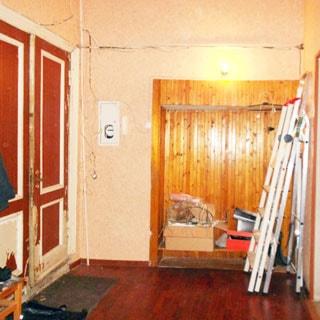 На фото: помещение прихожей, слева - входная двустворчатая деревянная дверь, справа от двери в ящике в стене - электросчетчик, справа от него - место для верхней одежды, правее у стены - лестницы-стремянки, полы - ламинат