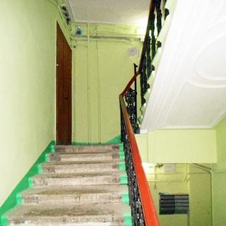 На фото: часть лестничного пролета, стены покрашены, потолки побелены, лестница чистая, перила металлические фигурные с деревянной накладкой, на нижней площадке на стене - блок почтовых ящиков