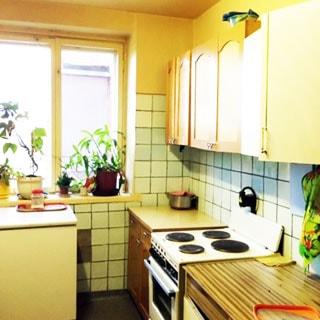 На фото: часть помещения кухни, окно, справа от окна вдоль стены - кухонные тумбы-столы и навесные шкафы, 4-комфорочная электрическая плита с духовкой, стены облицованы керамической плиткой в не полную высоту