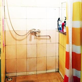 На фото: часть помещения душевой, в стену вмонтирован смеситель, спрва на стене полочка с ванными принадлежностями и зеркалом, пол и стены облицованы плиткой, слив устроен в полу