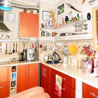 На фото: часть помещения кухни, от угла влево и вправо - встроенный кухонный гарнитур из тумб-столов с общей столешницей и навесных шкафов, в правой секции ближе к углу - мойка со смесителем, на стене - полки с кухонной мелочью и зеркало, в левой секции - электрическая варочная поверхность, над ней - вытяжка, справа от вытяжки на стене - часы, на потолке - люстра