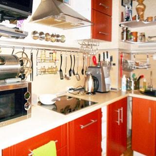 На фото: часть помещения кухни, от угла влево и вправо - встроенный кухонный гарнитур из тумб-столов с общей столешницей и навесных шкафов, в правой секции ближе к углу - мойка со смесителем, в левой секции - электрическая варочная поверхность, над ней - вытяжка, левее - духовой шкаф, на нем - гриль, над ним - навесная стойка с видеоприставкой и телевизором, полы - плитка