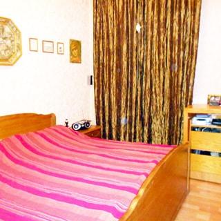 На фото: часть помещения жилой комнаты - спальни, окно закрыто шторой, слева у стены - двуспальная кровать, спрва от кровати - прикроватная тумбочка, справа от окна - туалетный столик с тумбочкой, полы - ламинат