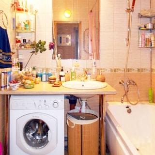 На фото: часть помещения ванной комнаты, прямо у стены - керамическая раковина со смесителем встроена в широкую столешницу на ножках, под столешницей слева от слива раковины - стиральная машина с фронтальной загрузкой, над раковиной - зеркало, справа - ванная со смесителем, стены облицованы керамической плиткой, на стенах в углах - проволочные полки для ванных принадлежностей