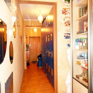 На фото: помещение вытянутого в длину коридора, переходящего в прихожую, спрва вдоль стены шкафы книжные и одежные, слева на стене - зеркала, полы- ламинат, на дальнем плане в центре - входная металлическая дверь, на потолке - люстра