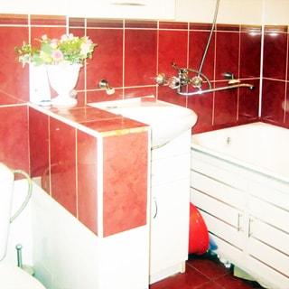 На фото: часть помещения совмещенного санузла, прямо в центре - керамическая раковина на тумбе белого цвета с дверцами, над раковиной - шкафчик, справа - ванная, смеситель общий для ванны и раковины, слева от раковины разделительный пристенок, за ним - унитаз-компакт, стены облицованы керамической плиткой, полы - плитка