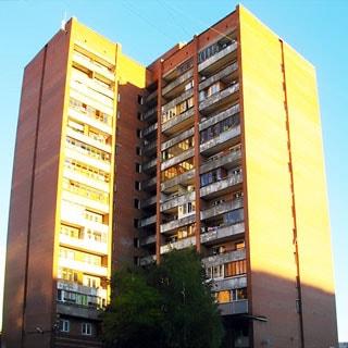 На фото: часть фасада кирпичного пятнадцатиэтажного многоквартирного жилого дома, лоджии, часть лоджий застеклена, благоустроенная придомовая территория, деревья