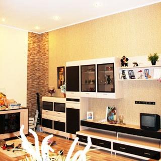 На фото: часть помещения жилой комнаты - гостиной, вдоль стены - современный мебельный гарнитур из тумб, навесных шкафов и полок, полы - ламинат, на потолке - точечные светильники