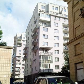 На фото: часть фасада многоэтажного жилого дома, фасад оштукатурен, балконы, перед домом припаркованы легковые автомобили, на переднем и заднем плане - соседние жилые многоэтажные дома