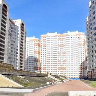 На фото: фасад шестнадцатиэтажного многоквартирного жилого дома, застекленные лоджии, благоустроенная придомовая территория, газоны, гравийные пешеходные дорожки, скамейки для отдыха