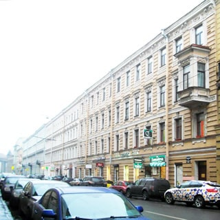 На фото: часть фасада кирпичного четырехэтажного многоквартирного дома, декоративная штукатурная отделка фасада, эркер, в цокольном этаже - коммерческие нежелые помещения, тротуар, проезжая часть, плотно припаркованные автомобили, на дальнем плане - колоннада Казанского собора