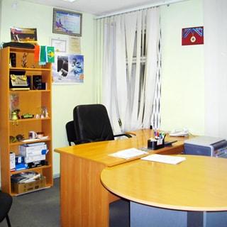 На фото: часть помещения нежилого помещения офисного типа, офисная мебель (книжный шкаф открытого типа, письменный стол, офисные кресла и стулья), принтер, на окне - вертикальные жалюзи