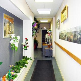 На фото: часть нежилого помещения - коридора или холла, стены окрашены, украшены эстампами и цветами, на полу - ковровая дорожка, на потолке - свтельники дневного света, на дальнем плане - входной холл и входная дверь