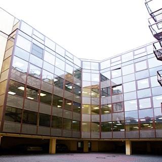 На фото: часть фасада шестиэтажного офисного здания со сплошным остеклением фасада, начиная с первого этажа, в цоколе - места для парковки автомобилей, территория двора вымощена тротуарным камнем, справа на фасаде - пожарная лестница