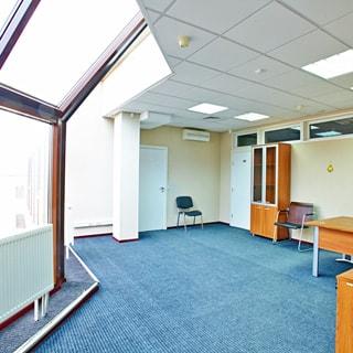 На фото: часть помещения офиса, слева большое панорамное окно от пола до потолка, полы - ковролин, потолки - подвесные с вмонтированными блоками ламп дневного освещения, на стене - кондиционер, две двери в соседние помещения, офисный шкаф, стулья, столы