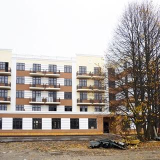 На фото: часть фасада нового пятиэтажного многоквартирного жилого дома, балконы, благоустроенная придомовая территория, деревья, перед домом небольшая свалка строительных ограждающий конструкций