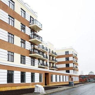 На фото: часть фасада нового пятиэтажного многоквартирного жилого дома, балконы, благоустроенная придомовая территория, газоны, тротуар, проезжая часть, на тротуаре поддон с емкостью для клея, на дальнем плане виден купол собора