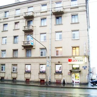 На фото: часть фасада кирпичного пятиэтажного многоквартирного жилого дома, балконы, перед домом - тротуар и проезжая часть, в цокольном этаже - магазин зоотоваров Ежкин кот, перед домом на стойке - дорожный знак остановки трамвая