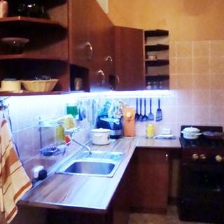 На фото: часть помещения кухни, встроенный кухонный гарнитур из тумб-столов с общей столешницей и навесных шкафов, в середине столешницы - металлическая мойка со смесителем, справа от угловой секции - 4-комфорочная газовая плита с духовкой, фартук облицован керамической плиткой и оборудован подсветкой