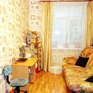 На фото: часть помещения жилой комнаты, окно, установлен стеклопакет, под окном - радиатор батареи центрального отопления, слева у стены - офисный стул на колесах, письменный стол, этажерка и комод, справа у стены - мягкий диван, стены оклеены обоями, полы - паркет или ламинат