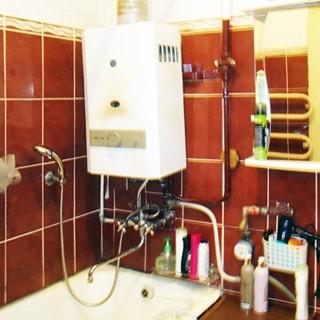 На фото: часть помещения ванной комнаты, прямо у стены в углу - ванная со смесителем, над ней - газовая колонка, правее на стене - шкафчик с зеркальными дверцами, стены облицованы керамической плиткой