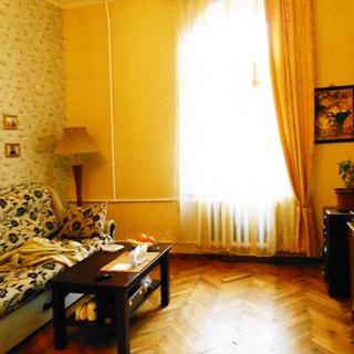 На фото: часть помещения жилой комнаты - гостиной, в центре - окно, под окном - радиатор батареи центрального отопления, слева от окна в углу - торшер, слева у стены - диван, перед ним - журнальный столик, полы - паркет